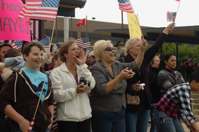 FORT HOOD, Texas-Family members cheer excitedly as buses containing 1st Air Cavalry Brigade service members, returning from Iraq, arrive at Cooper Field for a welcome home ceremony, April 19. The families had to wait longer than anticipated for the Soldiers to return due to volcanic activity in Europe.