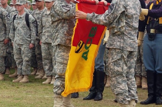 FORT HOOD, Texas-Surrounded by a formation of returning 1st Air Cavalry Brigade Soldiers and the 1st Cavalry Division honor guard, Col. Douglas Gabram, from Cleveland, commander, 1st ACB, 1st Cav. Div., uncases the brigade's colors with Command Sgt. Maj. Glen Vela, from Dallas, at a homecoming ceremony, April 19 at Cooper Field. The Soldiers were one of many groups returning from the Air Cav's year-long deployment to Iraq.