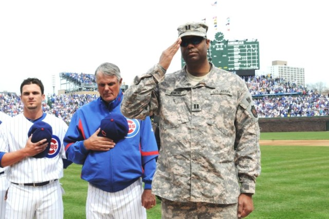 Captain Aaron Jenkins, Lombard Ill., salutes the American Flag next to Chicago Cubs Manager Lou Piniella and Shortstop Ryan Theriot, for their home opener at Wrigley Field, April 12, 2010.