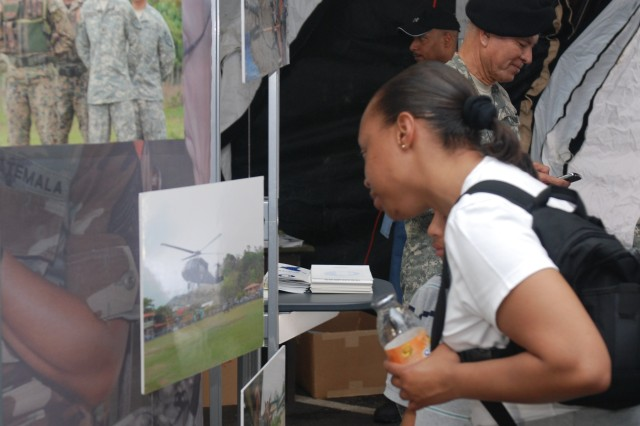 A Fiesta attendee studies photos of U.S. Army South's mission while visiting the command tent during the Fort Sam Houston Fiesta celebration held here April 18.  Fiesta began in 1891 when a group of ladies paraded in front of the Alamo in decorated horse-drawn carriages and threw flowers at each other. This tradition continues today andFiesta's Battle of Flowers parade is nowone of thenation's largest, second only to the Tournament of Roses. (U.S. Army photo by Ms. Arwen Consaul, U.S. Army South Public Affairs)