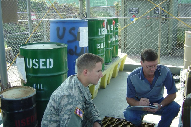 Mr. Chartier (right) inspects the 188th Military Police Company Hazardous Waste Accumulation Point at Camp Walker with PVT Mathew Hillbery. USAG Daegu strives to provide a clean environment for residents and a natural ecosystem by minimizing waste. Hazardous waste reduction is a garrison sustainability and EMS goal.