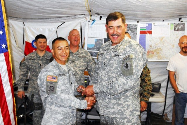 Maj. Gen. Simeon Trombitas, Deputy Commanding General, Joint Task Force-Haiti, hands Spc. Darwin Quinteros a coin after his re-enlistment April 7. Quinteros re-enlisted along with his wife, Spc. Erica Quinteros via teleconference in Haiti. (U.S. Army photo by Spc. William R. Begley/11th PAD)