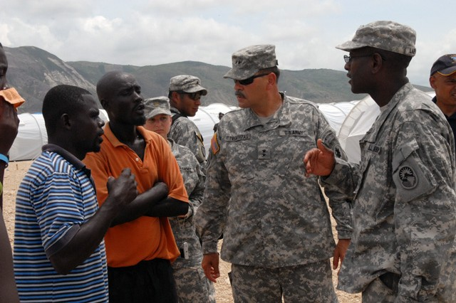 Maj. Gen. Simeon Trombitas, commander of JTF-Haiti, asks a few Haitians about the living conditions at the internally displaced persons camp, Corail Cesselesse. Trombitas took some time to walk around the camp and see the improvements made in the past few days.
