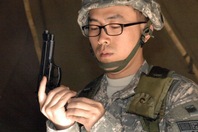 Son Sung-hyon of the 15th Korean Service Corps Co. from Red Cloud Garrison demonstrates how to unload an M9 pistol during Army Warrior Task weapon familiarization training at North Star Range in Uijeongbu April 15.