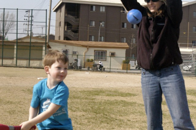 A participant of the Start Smart Baseball Program, Adian Smith, 4 years old, is hitting a ball in the air confidently while having private lessons with Karen Moore, Child Youth Program assistant from Child Youth and School Services on the Red Cloud Garrison softball field.