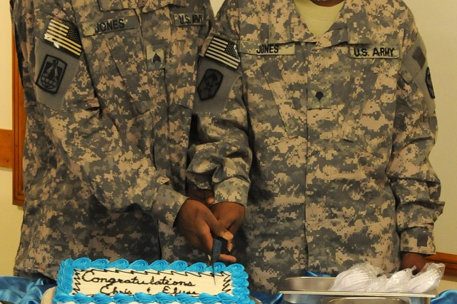 Sgt. Christopher Jones and Spc. Elyse Jones, a food service specialist and a logistics specialist both with the Headquarters and Headquarters Company, Special Troops Battalion, 15th Sustainment Brigade, cut their cake after renewing their wedding vows April 13 at Contingency Operating Location Q-West, Iraq. (U.S. Army photo by Staff Sgt. Rob Strain, 15th Sustainment Brigade Public Affairs)