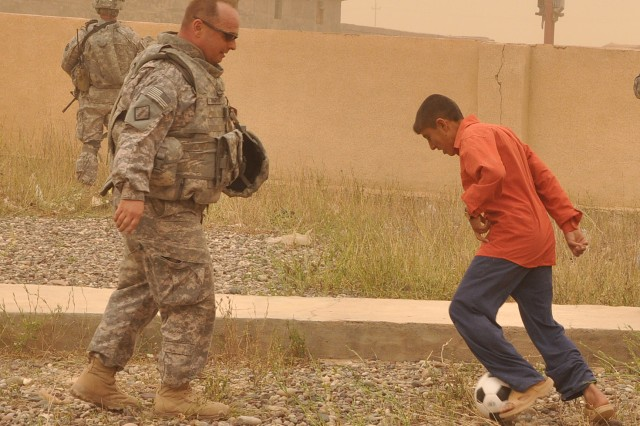 Maj. Scott Wadyko, a Jacksonville, Fla., native and 15th Sustainment Brigade, 13th Sustainment Command (Expeditionary), deputy operations officer, plays soccer with a local Iraqi boy during a visit to the school here April, 12. (U.S. Army photo by Staff Sgt. Matthew C. Cooley, 15th Sustainment Brigade public affairs)