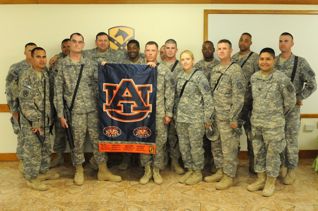 Members of the 40th Transportation Company, Special Troops Battalion, 15th Sustainment Brigade, pose with an Auburn University flag signed by Auburn faculty members, local politicians, U.S. Senators and the governor of Alabama during its presentation ceremony April 13 at the Wagonmaster Inn on Contingency Operating Location Q-West, Iraq. (U.S. Army photo by Staff Sgt. Rob Strain, 15th Sustainment Brigade Public Affairs)