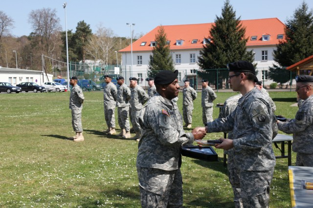Sgt. Rodney Rogers, a transportation noncommissioned officer with the 1177th Movement Control Team, left, receives a Welcome Home Warrior-Citizen Award April 18 during a ceremony at Daenner Kaserne in Kaiserslautern, Germany. The Kaiserslautern-based Army Reserve unit mobilized in February 2009 and deployed in support of Operation Iraqi Freedom.