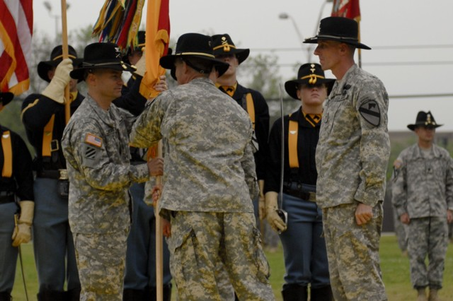 FORT HOOD, Texas-Col. Douglas Crissman (left), the commander for 3rd Brigade Combat Team, 1st Cavalry Division and a native of Burke, Va., receives the brigade's colors from Maj. Gen. Daniel Allyn, the commanding general of the division, during a change of command ceremony, April 16, on Cooper Field.