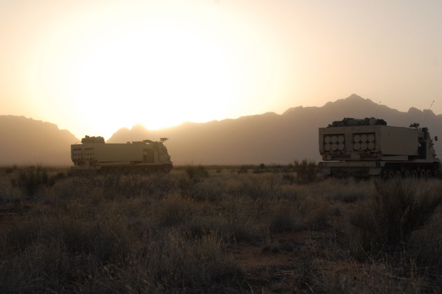 As the sun sets on Dona Ana Range, New Mexico, two M270 Multiple-Launch Rocket System, or MLRS, vehicles prepare for a night live-fire range during Operation Dragon Strike. The launchers are assigned to 3-13 FAR, 75th Fires Brigade, Fort Sill, Oklahoma.