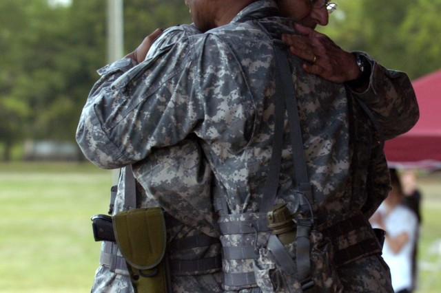 FORT BRAGG, N.C. -- Col. Ronald A. Maul, the retiring commander of the 44th Medical Brigade embraces his replacement, Col. Donald R. West at their change-of-command ceremony April 21. (U.S. Army photo by Spc. A.M. LaVey / XVIII Airborne Corps)