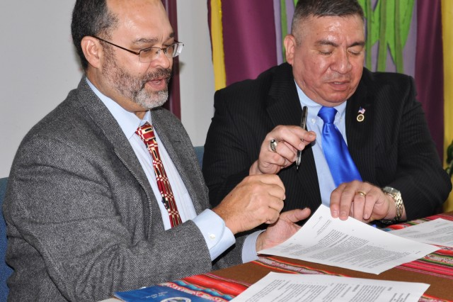 Stanley Green, executive director of the Mennonite Mission Network, hands the Alternative Service Employer Network agreement to Selective Service Director Lawrence G. Romo during a signing ceremony in downtown San Antonio, Texas, April 20.