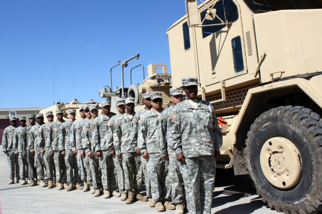Sgt. 1st Class Michelle Cunningham leads from the front as the instructors from the 96th Transportation Company, 553rd Combat Sustainment Battalion stand alongside one of their Heavy Equipment Transport tractor-trailers at a 4th Sustainment Brigade motor pool Mar. 4 at Fort Hood, Texas. (U.S. Army photo by Spc. Ann Marie White)