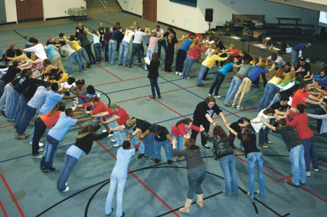 """Members of Teen Advisors create a """"leaning circle"""" to illustrate the support they can provide each other to do the right thing.  This year, 616 students from 24 local middle and high schools will speak to 5,500 of their peers in 18 area schools."""