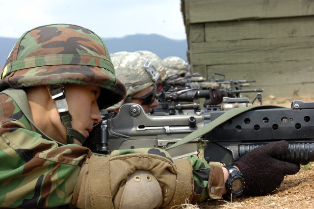 A ROK infantryman with 75th Mech. takes a support by fire position next to counterparts from 2-9th Inf., 1st HBCT during the Combined Arms Life Fire Exercise conducted April 15 at Rodriguez Range.