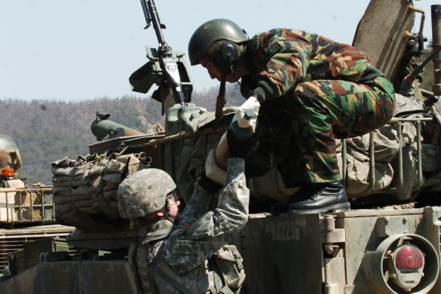 """A """"Manchu"""" Soldier with 2-9th Inf. helps a ROKA Soldier from 75th Mech. load mortar rounds onto his K242 Mortar Carrier prior to the Combined Arms Live Fire Exercise conducted April 15 at Rodriguez Range."""