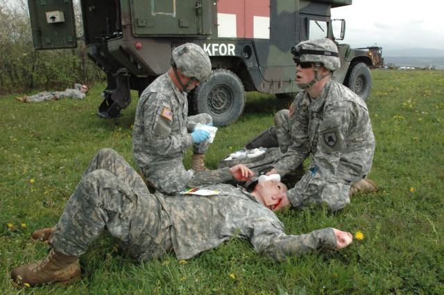 Spc. Michael Werner, a ground ambulance medic from Milnor, N.D., and fellow medic Sgt. Jack Brooks, Whitley City, Ky., provide first-aid to Spc. Dustin Engebretson, Fargo, N.D., who played the role of a Soldier with a severe facial injury, on April 16, when members of KFOR's Multinational Battle Group East's Task Force Med Falcon were faced with a challenging mass casualty exercises at Camp Bondsteel, Kosovo.
