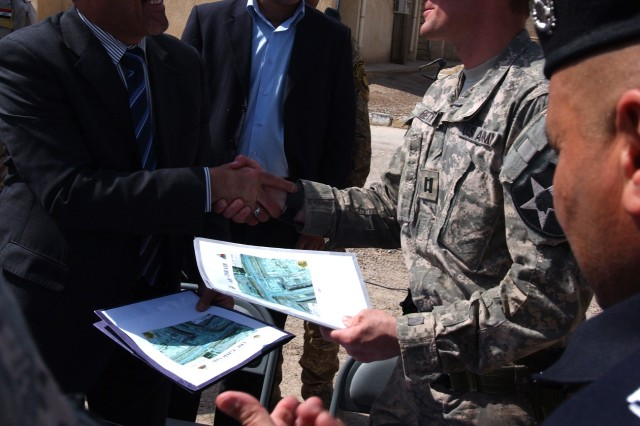 ABU GHRAIB, Iraq - Sameer Al-Haddad of the Ministry of the Interior and Capt. Joshua Betty, commander of Company C, 1st Battalion 38th Infantry Regiment, 4th Stryker Brigade Combat Team, 2nd Infantry Division, shake hands after signing over Joint Coordination Center Abu Ghraib to the Government of Iraq April 20. (U.S. Army photo by Sgt. Bryce Dubee, 4th SBCT PAO, 2nd Inf. Div., USD-C)
