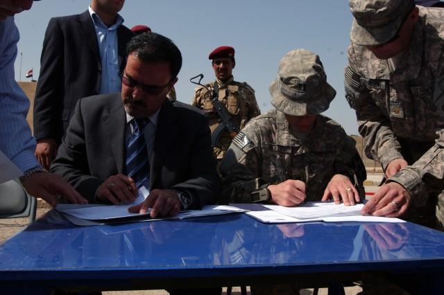 ABU GHRAIB, Iraq - Sameer Al-Haddad of the Ministry of the Interior, and Capt. Joshua Betty, commander of Company C, 1st Battalion, 38th Infantry Regiment, 4th Stryker Brigade Combat Team, 2nd Infantry Division, sign documents transferring authority of Joint Coordination Center Abu Ghraib from U.S. forces to the Iraqi government, April 20. (U.S. Army photo by Sgt. Bryce Dubee, 4th SBCT PAO, 2nd Inf. Div., USD-C)