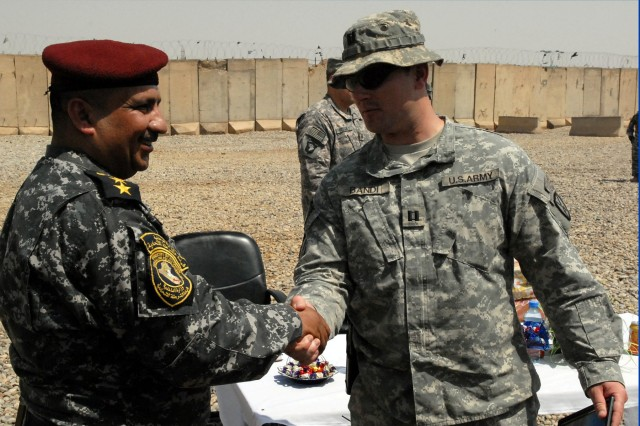 BAGHDAD - Capt. Matthew Bandi, commander of C Troop, 1st Squadron, 89th Cavalry Regiment, 2nd Brigade Combat Team, 10th Mountain Division, shakes hands with Col. Yousef M' Shutit Mohsin, commander of 1st Battalion, 3rd Brigade, 1st Iraqi Federal Police Division, after completing the transfer of Joint Security Station Salie at JSS Sallie April 20. (U.S. Army photo by Staff Sgt. Ryan Sabin, 2nd BCT PAO, 10th Mtn. Div., USD-C)