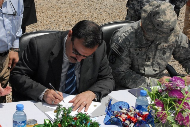 BAGHDAD - Sameer Al Haddad, the receivership secretariat for the Government of Iraq, and Capt. Matthew Bandi, commander of C Troop, 1st Squadron, 89th Cavalry Regiment, 2nd Brigade Combat Team, 10th Mountain Division, sign documents completing the transfer of Joint Security Station Salie from U.S. forces to Iraqi Security Forces at JSS Salie April 20. (U.S. Army photo by Staff Sgt. Ryan Sabin, 2nd BCT PAO, 10th Mtn. Div., USD-C)