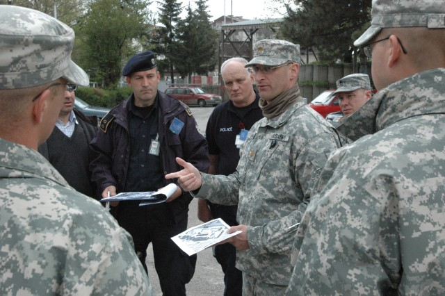 Maj. Shayne Simon, Alexandria, Minn., operations officer for Multinational Battle Group East, on April 20, explains the role that is planned for KFOR in an upcoming June joint exercise with the Kosovo Police and EULEX at Camp Montieth in Gjilan/Gnjilane, Kosovo. Lt. Naser Rahmani (center background), chief of operations with the Gjilan/Gnjilane Kosovo Police Service, listens intently.