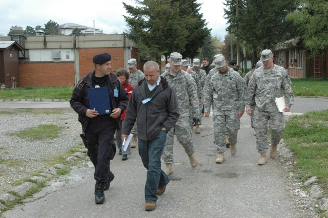 "Lt. Naser Rrahmani, chief of operations for the Gjilan/Gnjilane Kosovo Police Service, and translator Milaim Grabovci lead a group of KFOR Soldiers from Multinational Battle Group East during a ""walkthrough"" planning session April 20 at Camp Montieth in Gjilan/Gnjilane, Kosovo. The KFOR Soldiers, KP and EULEX used the opportunity to coordinate their roles for an upcoming joint exercise."