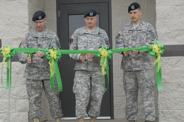 From left, CPT Brian Miller, COL Thomas Macdonald and SFC James Allred cut the ribbon Tuesday outside the new $2.6 million kennel and office complex on Fort Benning.
