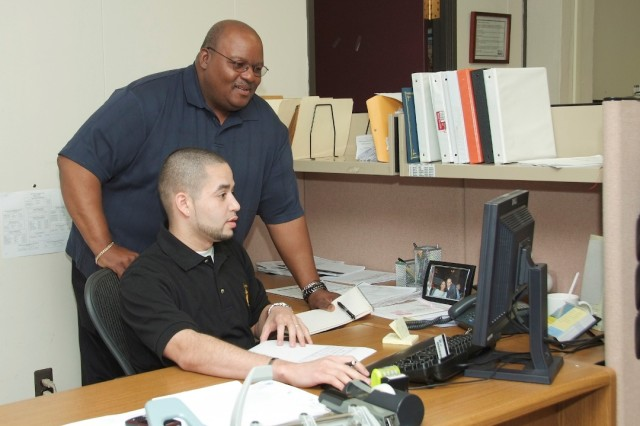 Central oversight and management of government inventory by way of property books and hand receipts is a crucial process within the Army. Above, Glenn Gordon, property book officer at Fort Monmouth, reviews an inventory database with Jose A. Rodriguez, Jr., who oversees the property book for CECOM Life Cycle Manangement Command.