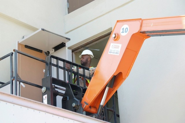 The proper manangement of government property is a major theme as Fort Monmouth approaches closure next year under Base Realignment and Closure (BRAC) law. Above, a member of the garrison's property book pick-up team maneuvers office equipment onto a crane. Such activity will be increasingly common as the year progresses.