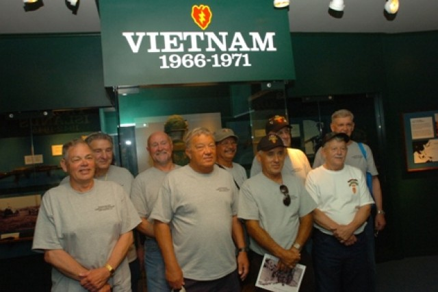 Nine Vietnam veterans stand before the 25th Infantry Division Museum's Vietnam exhibit, at Schofield Barracks, Hawaii, April 21. The veterans served with Company F, 50th Inf. Long Range Patrol, 75th Inf. (Ranger) Regiment, which was attached to the 25th Inf. Div. in Vietnam. During their visit the veterans from Co. F and their wives toured the base, observed Soldiers participating in the division's Best Warrior Competition and ate lunch with Soldiers in a dining facility.