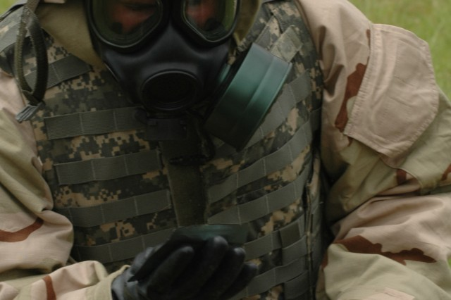 Spc. Andy James, a grenadier with Company B, 2nd Battalion, 27th Infantry Regiment, 3rd Brigade Combat Team, 25th Infantry Division, and a native of Leopold, Ind., disinfects his protective gear after a chemical attack during the division's Best Warrior Competition April 22 at Area X, Schofield Barracks, Hawaii. Soldiers and Noncommissioned Officers representing their units performed a variety of events during the competition held April 19-22, including taking an Army Physical Fitness Test, reflexive firing an M-4 rifle, completing common Soldier tasks, and appearing before a board.