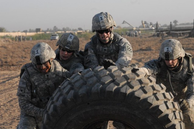 Soldiers representing 203rd Brigade Support Battalion, 3rd Heavy Brigade Combat Team, 3rd Infantry Division, flip a tire meant for a Mine-Resistant Ambush-Protected vehicle April 15, 2010, at a station during the best-squad competition at Contingency Operating Site Kalsu, Iraq. The competition tested the teamwork and physical abilities of teams representing the Sledgehammer Brigade's six battalions.