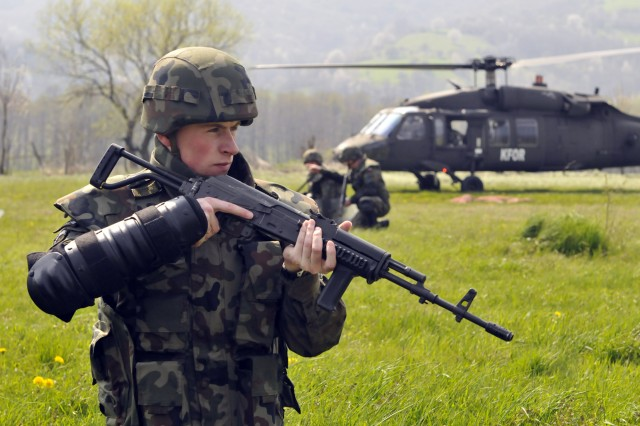 A Soldier with the Polish contingent of Multinational Battle Group East pulls security as other Soldiers dismount from helicopters during a Quick Reaction Force exercise at Novo Brdo, Kosovo, on April 21.