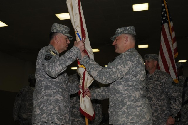 Col. Brian R. Haebig, the outgoing commander of the 402nd Army Field Support Brigade out of Rock Island, Ill., and an Oshkosh, Wis., native, hands the flag to Maj. Gen. James E. Rogers, commander of the 1st Sustainment Command (Theater) out of Fort Bragg, N.C., and a Jackson, Ala., native, during the change of command ceremony April 21 at Morale, Welfare and Recreation east at Joint Base Balad, Iraq.