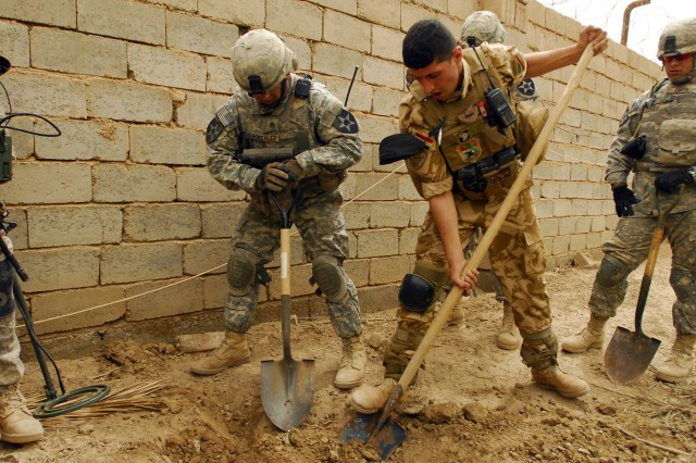 ZAIDON, Iraq - Staff Sgt. Yulier Gonzalez, a platoon sergeant with Company C, 4th Battalion, 9th Infantry Regiment, 4th Stryker Brigade Combat Team, 2nd Infantry Division, and Pvt. Muhamid, a Soldier with 4th Battalion, 24th Brigade, 6th Iraqi Army Division, put their shovels to work during a joint cache search April 12. (U.S. Army photo by Spc. Luisito Brooks, 4th SBCT PAO, 2nd Inf. Div., USD-C)