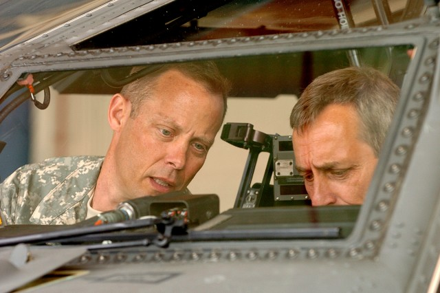 FORT HOOD, Texas-Col. Shane Openshaw (left), the Apache project manager, of Clearfield, Utah, shows Jim Loyco, of Northrop Grumman Contracts, the AH-64D Apache Longbow's features, during a site visit, April 20, here.