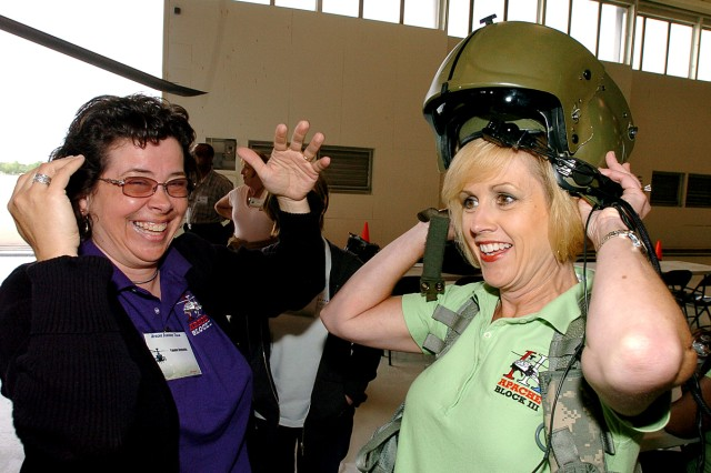 FORT HOOD, Texas-Yvonne Reynolds (left), an Army Contracting Command contracting officer, of Huntsville, Ala., laughs at the tight fit when Lisa Stangle, AMCOM's director of Apache Contracts, tries on an Apache pilot's helmet during a site visit, April 20, at Fort Hood, Texas.