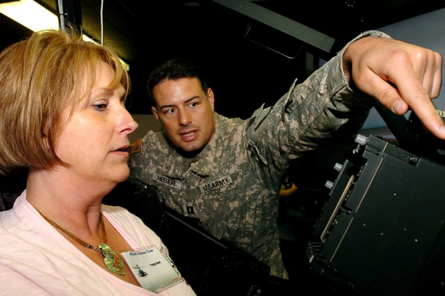 FORT HOOD, Texas-Capt. Jake Huber, 21st Cavalry Brigade (Air Combat), from St. Louis, shows Peggy Hunt, an Army Contracting Command contracting officer, how to operate an AH-64D Apache Longbow simulator during a site visit, April 20, at Fort Hood, Texas.