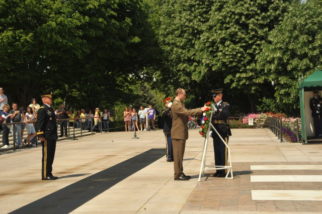 Mark Grimmette (center), a member of the U.S. 2010 Olympic Luge team, with the assistance of a Tomb Guard, lays a wreath at the Tomb of the Unknowns at Arlington National Cemetery on April 22, 2010. The wreath was laid on behalf of the 2010 U.S. Olympic Luge Teams. Maj. Gen. Karl R. Horst (left), commander, Joint Force Headquarters National Capital Region and The U.S. Army Military District of Washington looks on. Grimmette, was the United States flag bearer at the 2010 Winter Olympics in Vancouver.