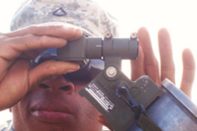 Pfc. Alejondro Sears looks through the bore sight of a 120mm mortar tube to sight in the weapon during training on the parade field at Camp Guernsey, Wyo. April 11.