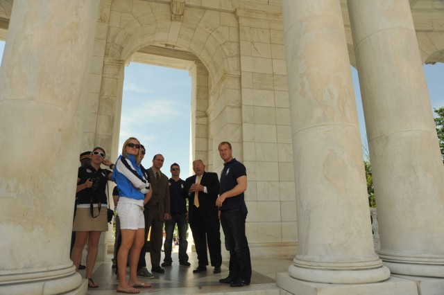 Members of the 2010 U.S. Luge Teams listen as Jack Metzler (second from right), superintendent of Arlington National Cemetery, gives a tour in the Memorial Amphitheater on April 22, 2010.