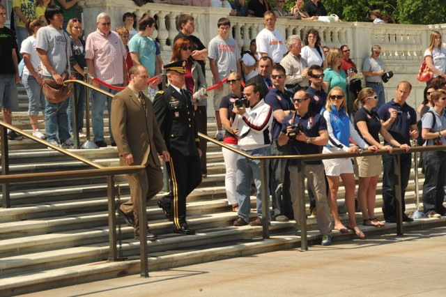 Mark Grimmette (left), a member of the U.S. 2010 Olympic Luge team and Maj. Gen. Karl R. Horst (right), commander, Joint Force Headquarters National Capital Region and The U.S. Army Military District of Washington render honors as taps is played at the wreath laying ceremony on April 22, 2010. Grimmette laid on behalf of the 2010 U.S. Olympic Luge Teams. He was the United States flag bearer at the 2010 Winter Olympics in Vancouver.