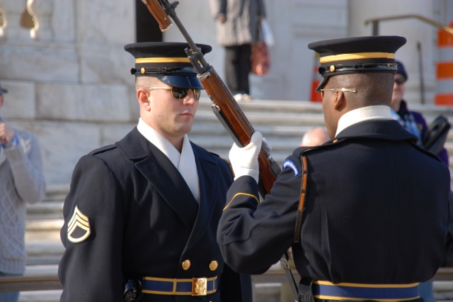 Staff Sgt. Ty Vickers dismisses Pfc. Rikki Reed from his post while changing the guard at the Tomb of the Unknowns. In the winter, the guard is changed every hour, but is changed every half hour in the summer.