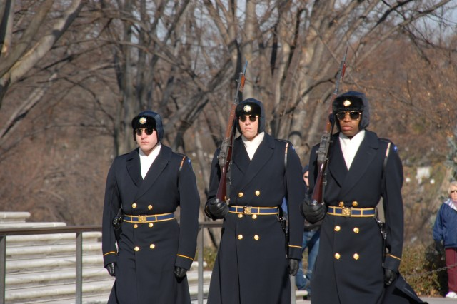 Tomb sentinels in cold-weather gear change guard duties at the Tomb of the Unknowns.