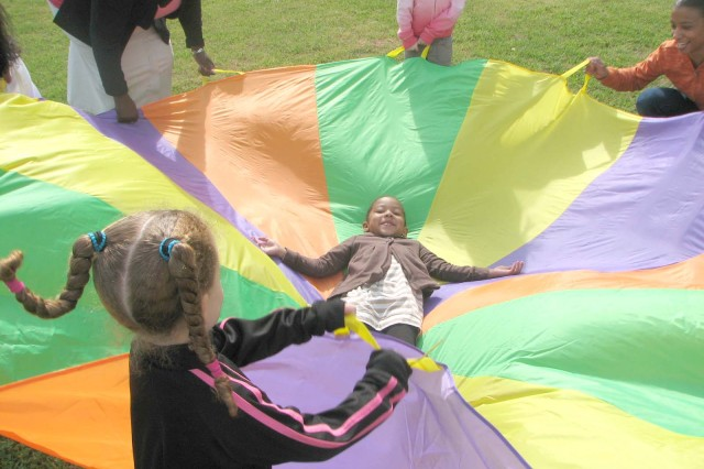 Makaila Penman, 4, daughter of Pfc. Nefertiti Murray, a signal support specialist with Headquarters and Headquarters Company, Third Army, lays in the center of a parachute while her classmates flap in around her. Penman is a member of the Child, Youth and Schools Services pre-kindergarten class. The children wrapped themselves inside the parachute to experience how a caterpillar feels inside a cocoon before turning into a butterfly.