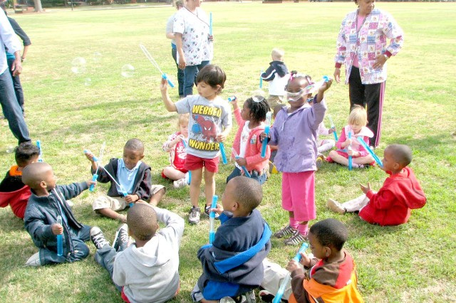 Children from the CYSS preschool class socialize and play with bubbles. After the event, several bubble wands were given to the school so kids could have fun later.