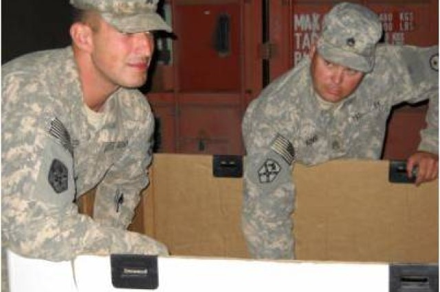 Sgt. Andrew Baker, a mechanic from New Philadelphia, Ohio, and Staff Sgt. Dwayne King, a truck driver from Ohio, both from the 1483rd Transportation Company, 541st Combat Sustainment Support Battalion, 15th Sustainment Brigade, 13th Sustainment Command (Expeditionary), empty supplies and other materials from a tri-wall as part of their new duties with the brigade's Mobile Redistribution Team at Camp Taji, Iraq.
