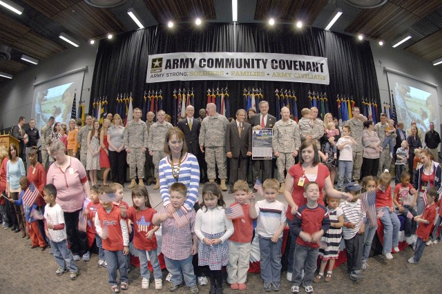Participants gather on stage after the signing of the Puget Sound Army Community Covenant at Clover Park Technical College in Lakewood, Wash., on May 2, 2008.